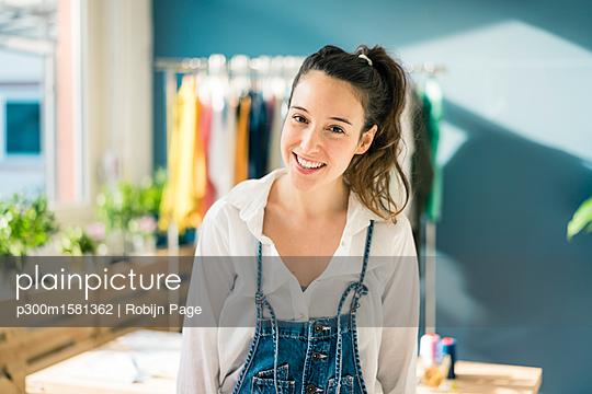Portrait of smiling fashion designer in her studio - p300m1581362 von Robijn Page