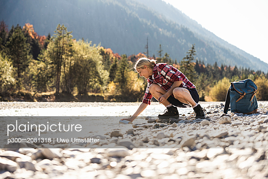 Austria, Alps, woman on a hiking trip having a break at a brook - p300m2081318 by Uwe Umstätter