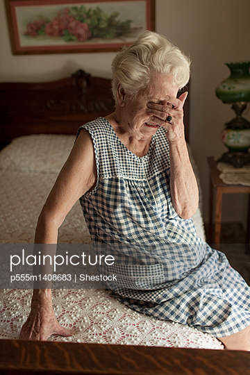 Sad older woman crying on bed