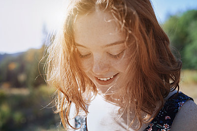 Smiling young woman with freckles looking down - p1023m2088002 by Arman Zhenikeyev