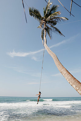 Full length of woman swinging from palm tree at beach against sky, Sri Lanka - p300m2199189 by letizia haessig photography