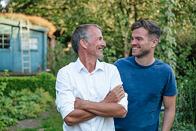 Father with arms crossed looking at son while standing in garden - p300m2277249 by Gustafsson
