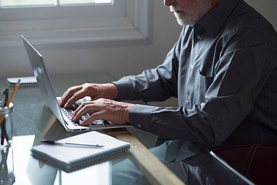 Senior male business professional working on laptop at table - p300m2277652 by Simona Pilolla