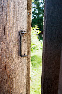 Open wooden door with hook - p312m1121453f by Lina Karna Kippel
