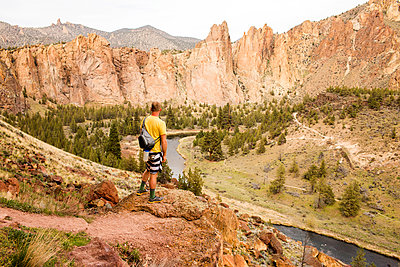 Caucasian hiker admiring hills and stream in desert landscape, Smith Rock State Park, Oregon, United States - p555m1412141 by Adam Hester
