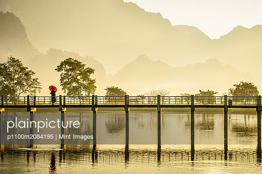 Mountains and bridge reflected in still lake, Hpa an, Kayin, Myanmar,Hpa an, Kayin, Myanmar - p1100m2084195 by Mint Images