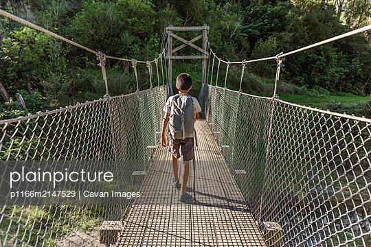 Tween boy with backpack walking on wooden bridge - p1166m2147529 by Cavan Images