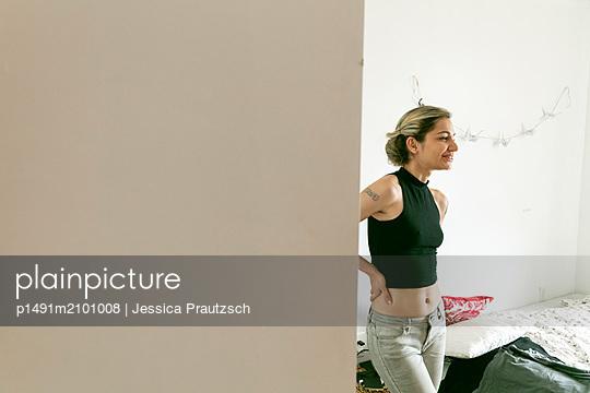 Frau steht lachend in Schlafzimmer - p1491m2101008 von Jessica Prautzsch