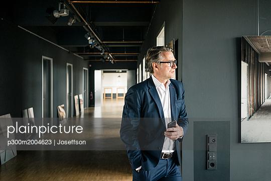 Mature businessman standing in office holding cell phone - p300m2004623 von Joseffson