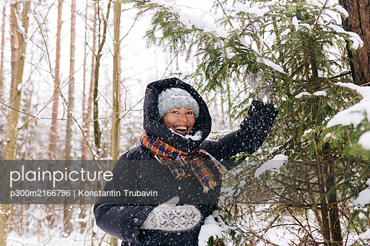 Portrait of laughing woman in winter forest enjoying snowfall - p300m2166796 by Konstantin Trubavin