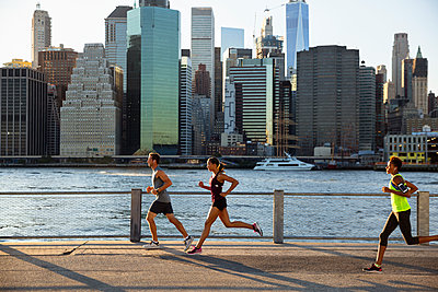 Athletes running on promenade by river against city - p1166m1174759 by Cavan Images