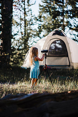 Girl holding binoculars on tripod while standing at campsite - p1166m1489786 by Cavan Images