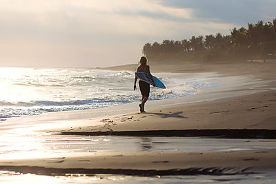 Indonesia, Bali, young surfer walking on beach - p300m1536308 by Konstantin Trubavin