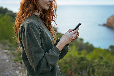 Redheaded young woman using cell phone at the coast, Ibiza, Spain - p300m2159890 by VITTA GALLERY
