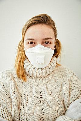 Portrait of blond woman wearing FFP2 mask at home - p300m2188594 by Sandra Bielmeier