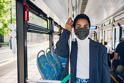 Businesswoman standing by leaning on pole in bus during COVID-19 - p300m2241850 by Katharina und Ekaterina