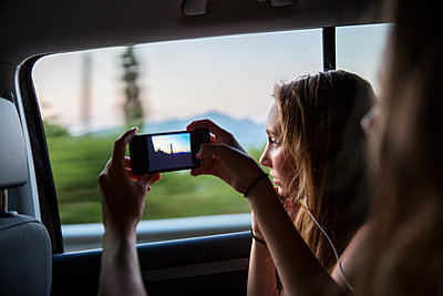 Woman taking pictures with smartphone in car - p312m1114099f by Lena Granefelt