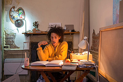 Woman reading book at desk - p429m767839 by dotdotred