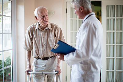Doctor talking to patient using walker - p555m1305748 by Resolution Productions