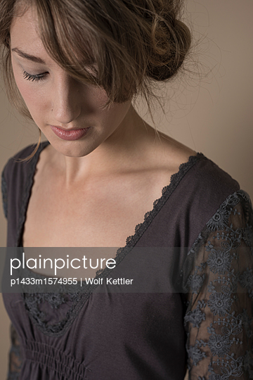 Young woman in casual dress with lace arms, looking down. - p1433m1574955 by Wolf Kettler