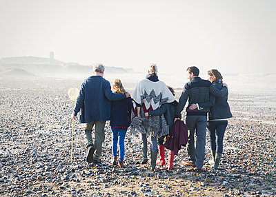 Multi-generation family walking in a row on beach - p1023m1106077f by Sam Edwards