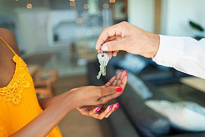 Close up man giving house keys to woman - p1023m2196705 by Paul Bradbury