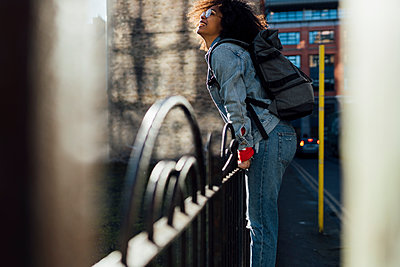 Smiling afro woman with backpack standing by railing in city - p300m2213921 by Boy photography