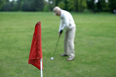Älterer Mann beim Putten, rote Fahne im Vordergrund - p4902230 von Stock4B