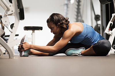 Mixed Race woman stretching legs on floor at gymnasium - p555m1303486 by JGI/Tom Grill