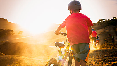 Mixed race boy riding dirt bike on track - p555m1304737 by Sollina Images
