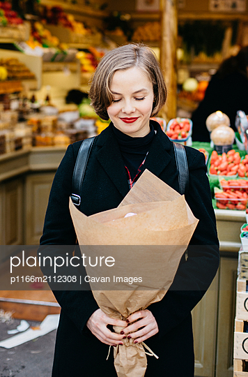 Woman with eyes closed holding bouquet while standing against market stall in city - p1166m2112308 by Cavan Images