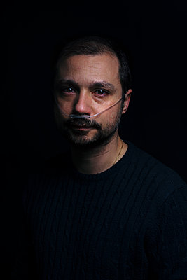 Portrait of a man wearing a nasal cannula  - p1165m2205013 by Pierro Luca