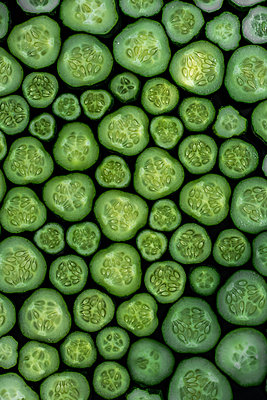 Overhead view of cucumber slices arranged on table - p1166m2024970 by Cavan Images