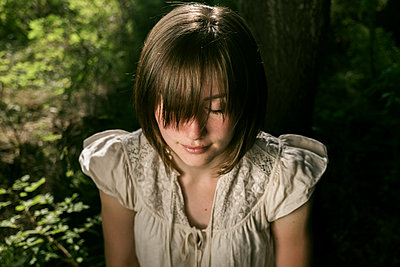 High angle view of young woman with eyes closed and bangs in forest - p1166m2025101 by Cavan Social