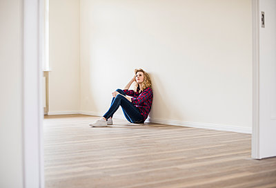 Young woman in new home sitting on floor - p300m1459914 by Uwe Umstätter