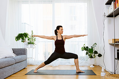 Woman practicing yoga at home - p300m2121887 by Sofie Delauw