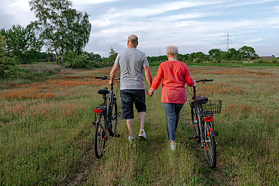 Mature couple holding hands while wheeling bicycle at field - p300m2267083 by Oxana Guryanova