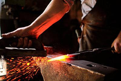 Male expert forging overheated metal on anvil at blacksmith shop - p300m2281445 by Antonio Ovejero Diaz