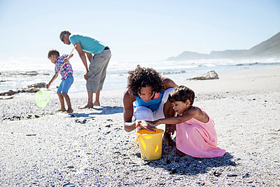 Mixed race family playing on beach - p555m1410113 by Resolution Productions