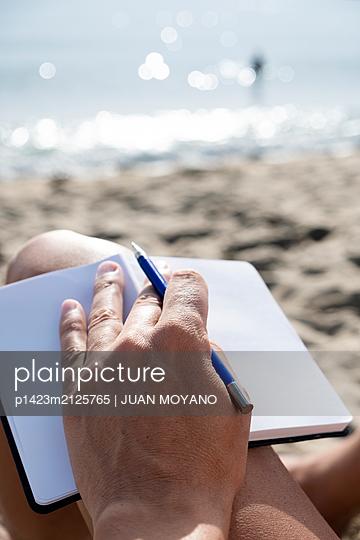 Man with a notebook on the beach - p1423m2125765 von JUAN MOYANO
