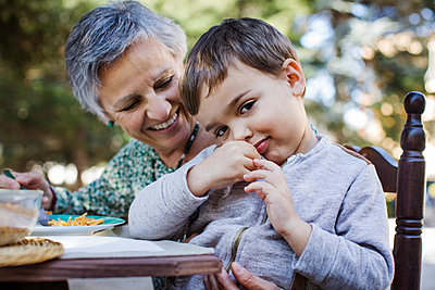 Portrait of cute boy sitting with grandmother at outdoor table - p1166m1145248 by Cavan Images