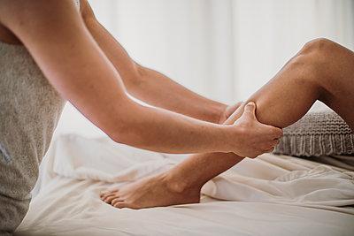 A massage therapist treats the legs of a female client - p1166m2107022 by Cavan Images