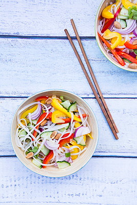 Bowls of glass noodle salad with vegetables on wood - p300m1191989 by Larissa Veronesi