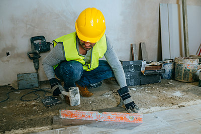 Construction worker placing flooring with a mallet - p300m1355908 by Kiko Jimenez
