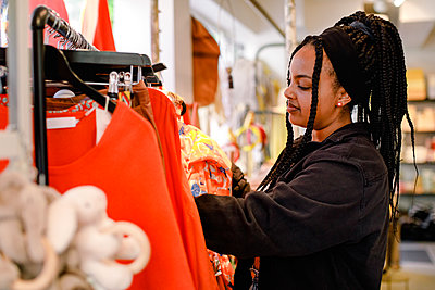 Side view of young woman at fashion store - p426m2213466 by Maskot