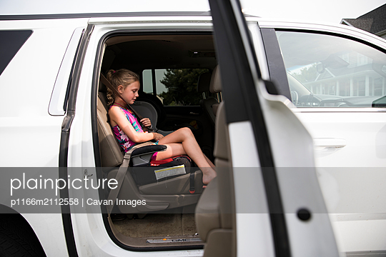 Full Body Young Blonde Girl with Curly Hair in Backseat of White SUV - p1166m2112558 by Cavan Images