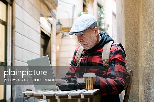Portrait of senior man sitting at street cafe using laptop, Barcelona, Spain - p300m2167158 by COROIMAGE