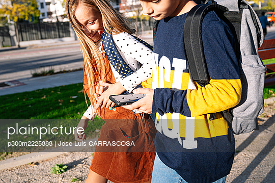 Sibling holding hands while using smart phone walking in public park on sunny day - p300m2225888 by Jose Luis CARRASCOSA
