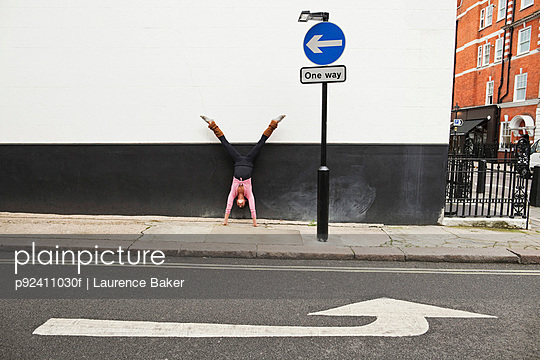 Woman performing handstand on pavement - p92411030f by Laurence Baker