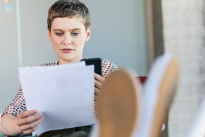Businesswoman reviewing document in office - p300m2214115 by Uwe Umstätter